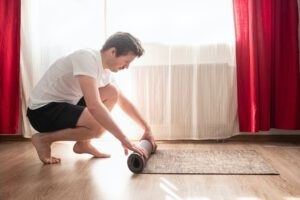 yoga man rolling yoga mat after training at home.