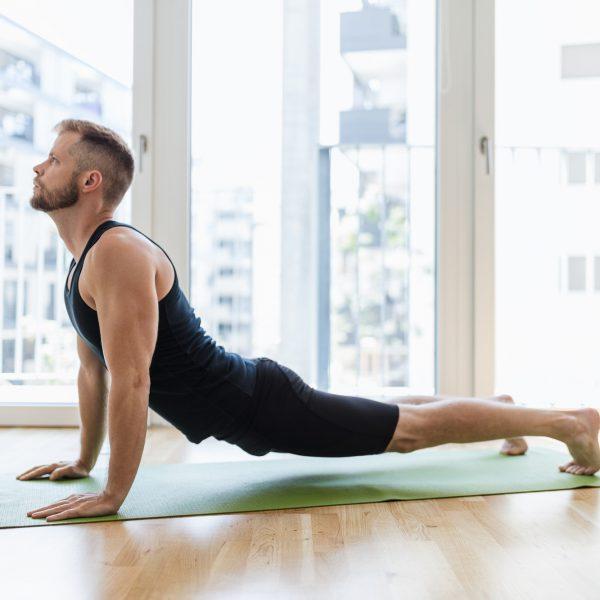 Man practicing yoga at his home